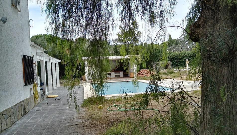 El xalet té un ampli jardí amb piscina i presenta un lamentable estat de deteriorament.