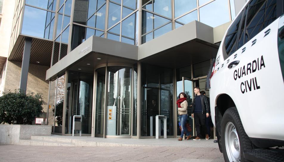 Treballadors sortint de Comsa i agents de la Guàrdia Civil custodiant la porta d'entrada de l'edifici aquest dijous.