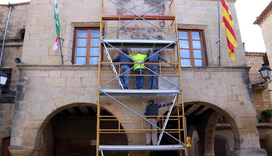 La façana en el moment en el qual els operaris de la brigada municipal desmuntaven l'última peça del plafó que tapa el mural.