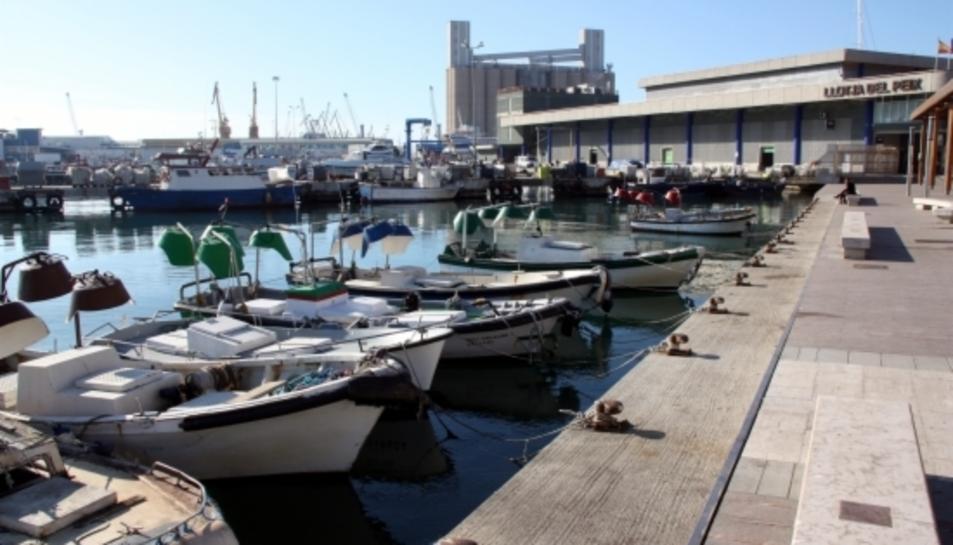 Barques de pescadors al barri del Serrallo de Tarragona, amb l'edifici de la Llotja de Peix al fons.