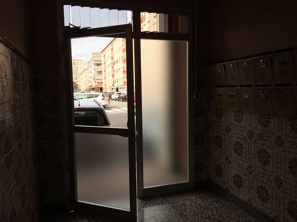 El vidre de la porta de l'edifici B de Sant Marc, amb algun pis ocupat, està trencat.