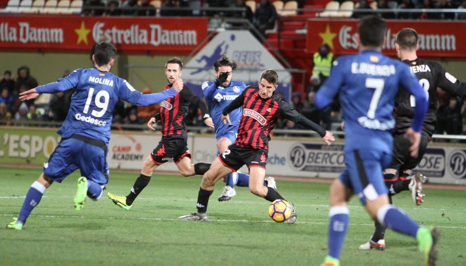 Campins, al centre, en una acció durant el CF Reus-Getafe, sota la mirada de Jorge Miramón.
