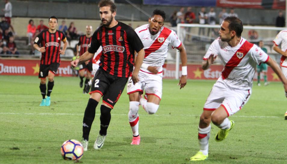 Benito, en primer terme, condueix la pilota sota la mirada de Folch, a l'anada contra el Rayo.
