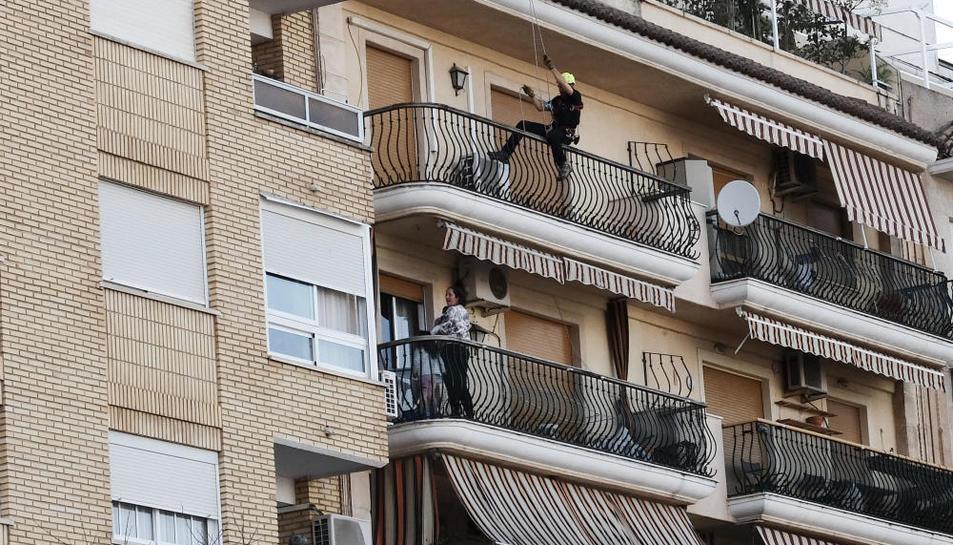 El policia acostant-se al balcó, on hi havia la dona amb els seus dos fills.