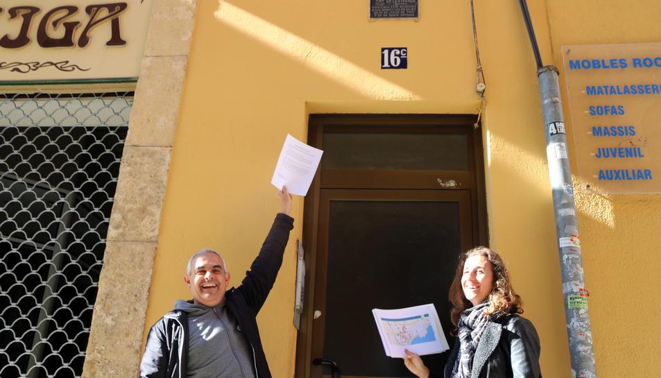 Pla contrapicat dels regidors de la CUP de Tarragona, Laia Estrada i Jordi Martí, sota una de les plaques amb simbologia franquista del carrer Reding de Tarragona. Imatge del 22 de març del 2017