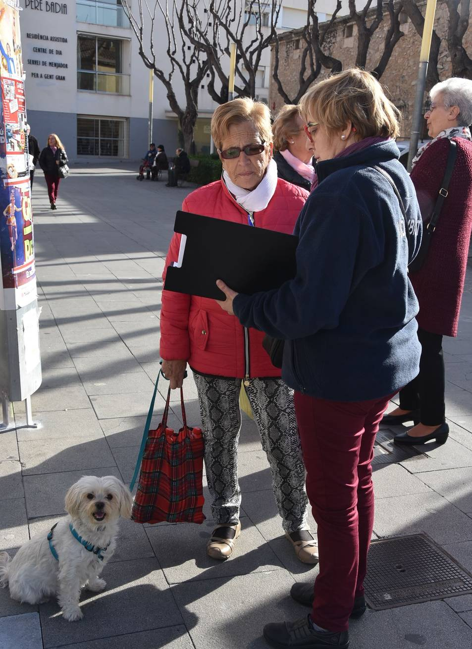 Una agent cívica ofereix informació a una dona que passeja amb el seu gos.