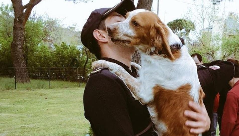 Un agent agafant un gos en braços.