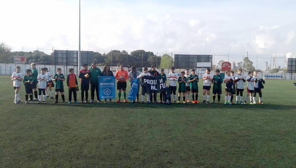 Els jugdors dels dos equips, mostrant la pancarta antiviolència.