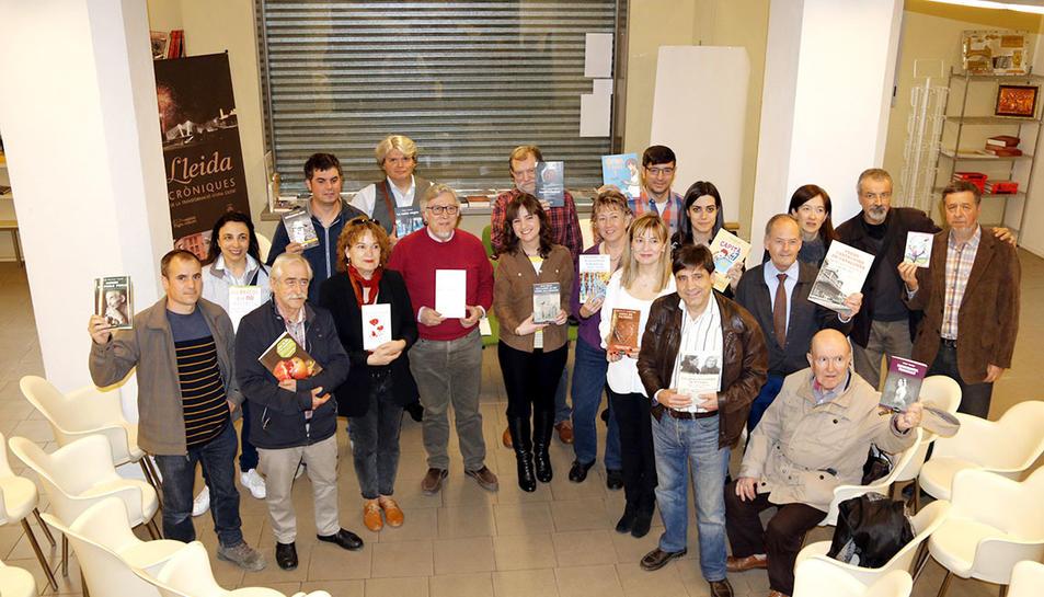 Imatge de grup d'una vintena d'escriptors, reunkts a la seu de l'editorial Pagès editors per presentar novetats per Sant Jordi