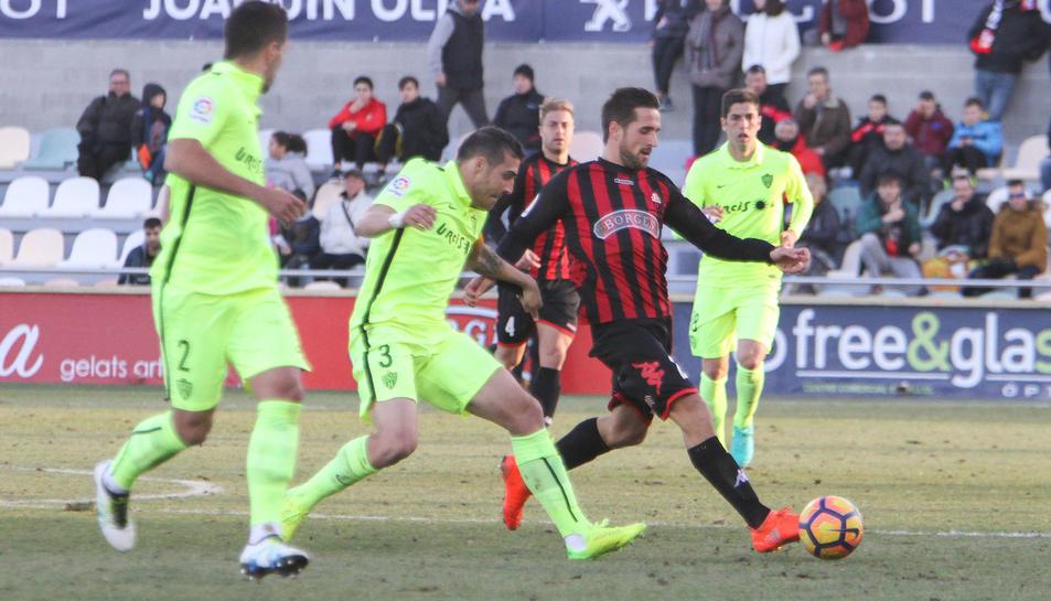 L'atacant del CF Reus Jorge Miramón condueix la pilota sota la pressió de rivals de l'Almeria.