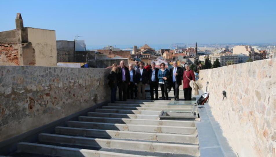 Foto de família a la zona restaurada de les muralles amb el director dels serveis territorials del Departament de Cultura, Jordi Agràs i la consellera de Patrimoni de l'Ajuntament de Tarragona, Begoña Floria.