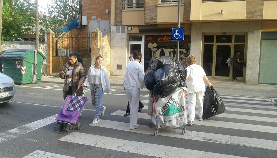 Empleades traslladen les bosses a l'altre costat de la calçada.