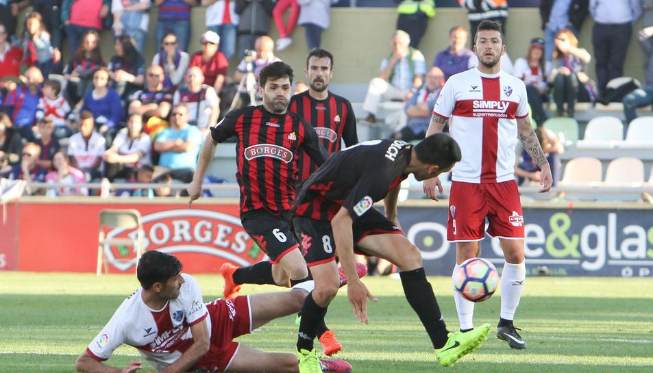 El capità Ramon Floch, en primer terme, durant un instant del partit contra l'Osca, sota la mirada dels també roig-i-negres Vítor Silva i Aritz López Garai.