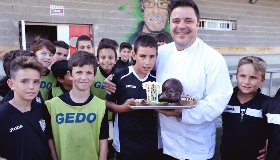 El petit Javier somriu rodejat dels seus amics i companys.
