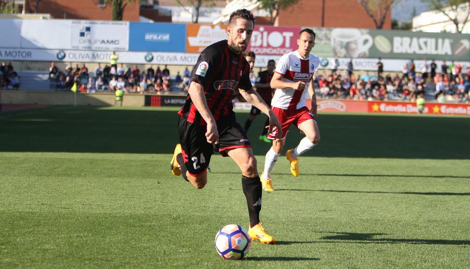 Jorge Miramón condueix la pilota durant un instant de l'enfrontament d'aquest diumenge, sota la mirada d'un oponent de l'Osca.