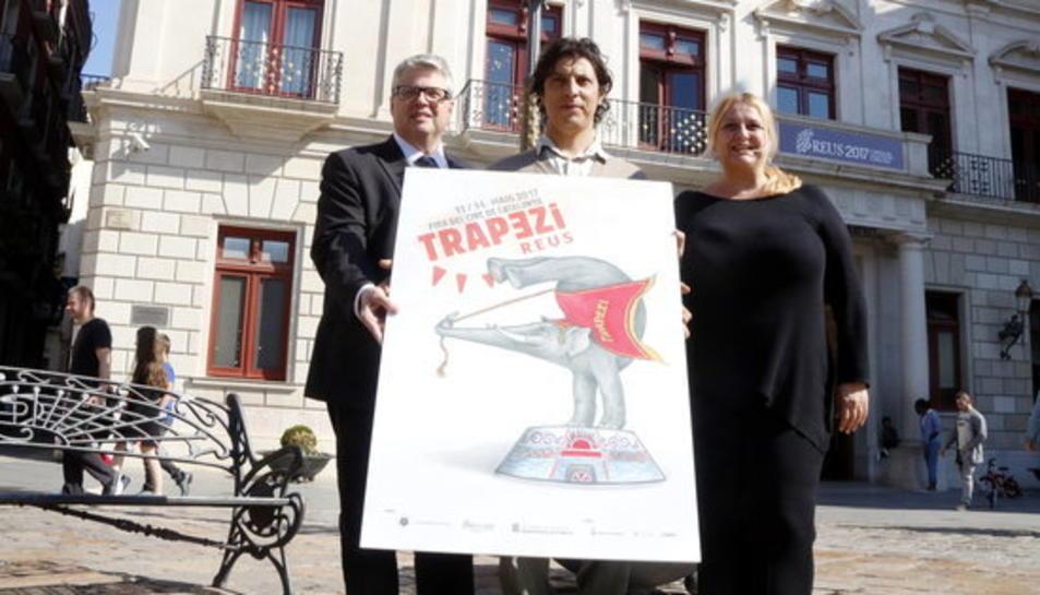 El director artístic del Trapezi, Leandro Mendoza, sostenint el cartell de la 21a edició amb el director dels serveis territorials de Cultura, Jordi Agràs, i la regidora de Cultura de Reus, Montserrat Caelles.