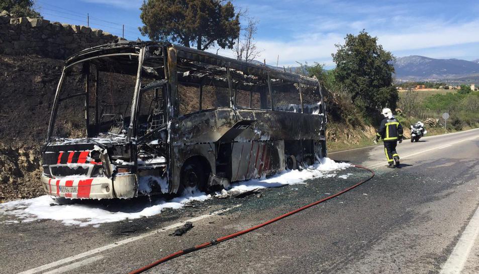Un efectiu dels Bombers remulla l'autobús calcinat a Guadarrama. pla general del 15 d'abril del 2017