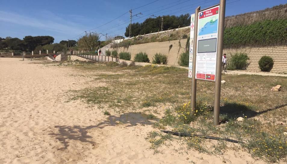 L'aigua escapa sota el cartell de platja blava.