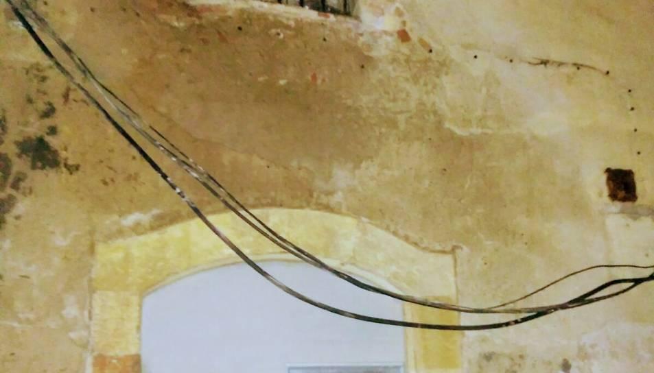 El cablejat arrencat penja de la façana.