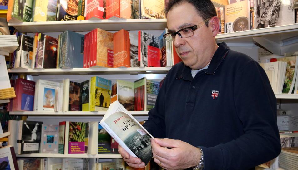 Pla mig d'Octavi Serret, enmig dels llibres del seu establiment de Vall-de-roures, fullejant un exemplar del 'Camí de Sirga' de Jesús Moncada. Imatge del 21 d'abril de 2017 (horitzontal)