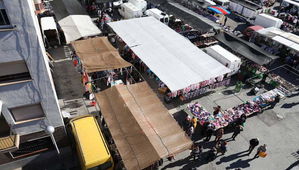 Furgonetes i parades a tocar de les façanes dels edificis, un dia del mercadet de Bonavista.