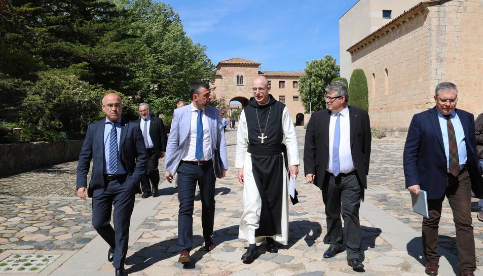 El conseller de Cultura, Santi Vila, amb l'abat de Poblet, Octavi Vilà, i el director de l'Arxiu Nacional de Catalunya, Francesc Balada, entre altres autoritats, caminant per l'exterior del Monestir de Poblet.