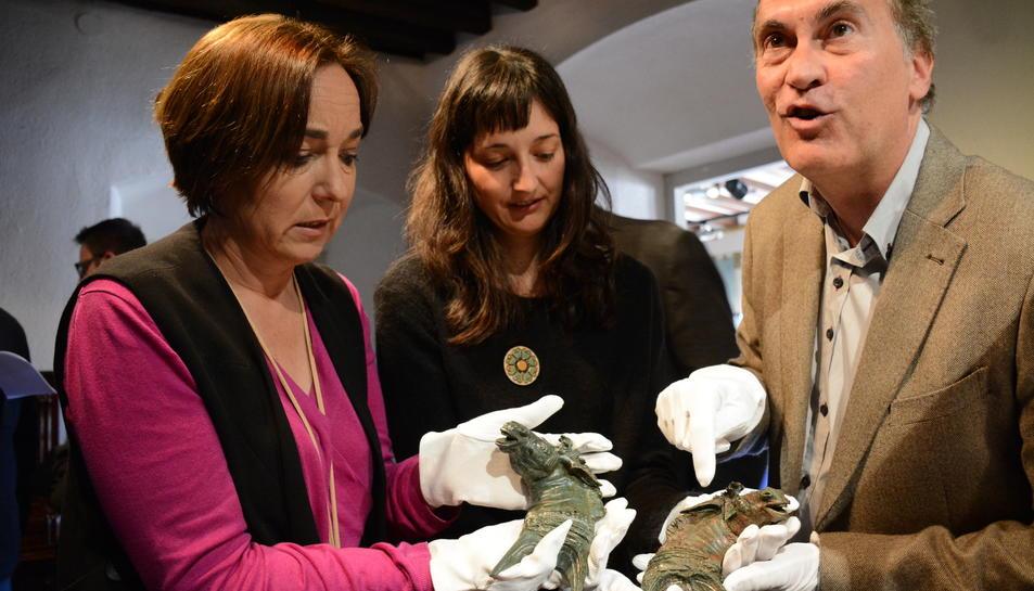 La consellera de Patrimoni, Begoña Floria; el restaurador de les peces, Pau Arroyo i l'arqueòloga responsable de la intervenció arqueològica, Judit Ciurana, sostenint els caps de mula recuperats.