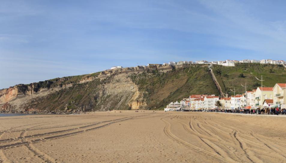 Van ser arrossegats per les onades en una platja deNazaré, al nord de Lisboa.