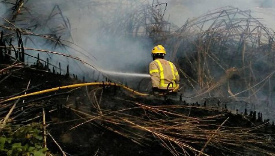 Imatge d'un bomber duent a terme les tasques d'extinció en l'incendi de Vilabella.