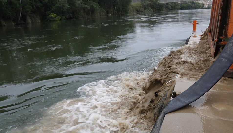 El moment en què s'aboquen tones d'argila i sorra al riu Ebre.