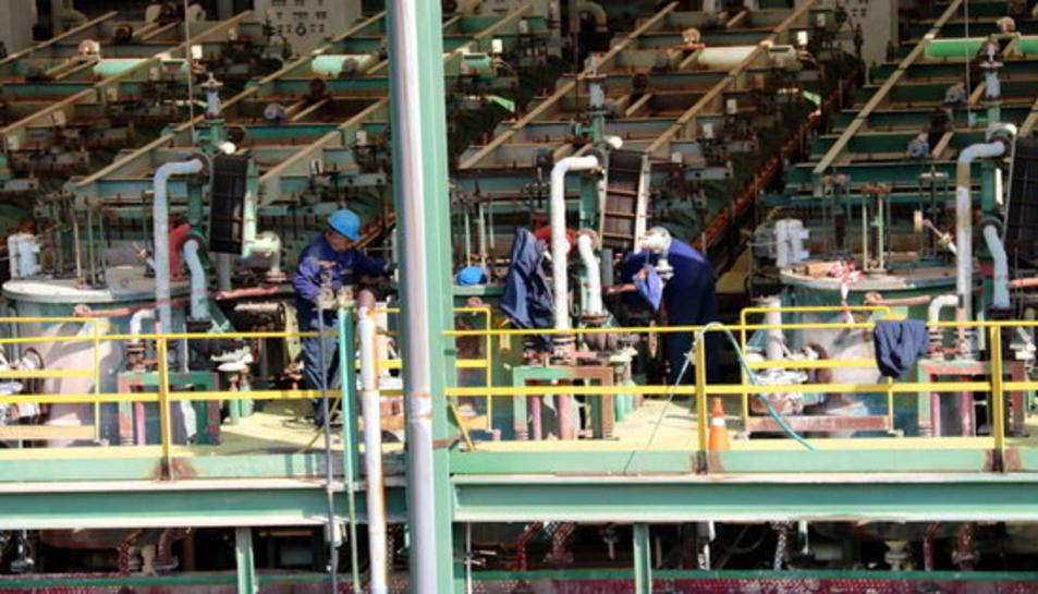 Pla detall d'uns treballadors operant a la planta de clor que Ercros tancarà al desembre d'aquest any.