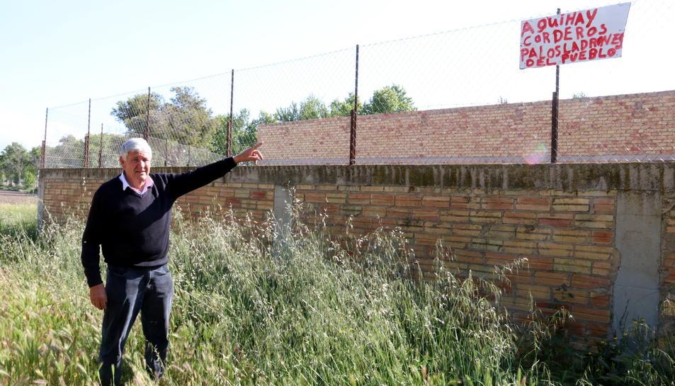 Aurelio Tena, ramader de l'Aldea, assenyalant un cartell contra els lladres que ha penjat al seu corral.
