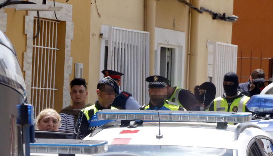 Agents dels Mossos i la Guàrdia Urbana emportant-se detinguts una dona i noi -a l'esquerra de la imatge-.