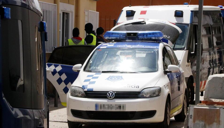 Els Mossos i la Guàrdia Urbana de Reus davant del domicili on s'ha dut a terme un operatiu antidroga, amb un vehicle policial en primer terme.