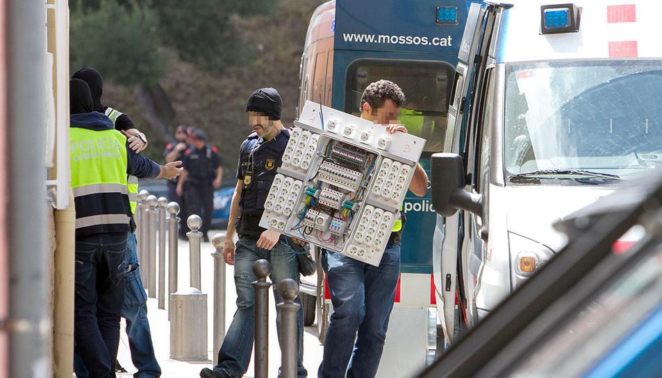 Un agent amb una bossa de supermercat plena de plantes de marihuana.