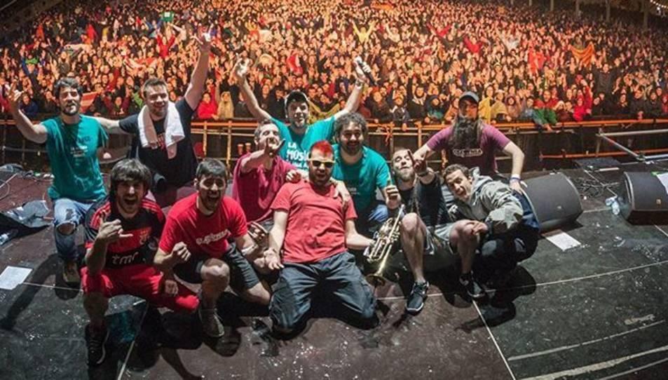 El grup al final d'un concert sobre l'escenari.