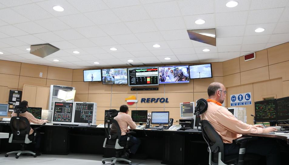 Pla general de la sala de control 24 hores de polipropilè de Repsol a Tarragona amb la nova il·luminació LED que reprodueix la llum natural, i de tres treballadors a la sala, davant les pantalles, en una imatge del 5 de maig del 2017