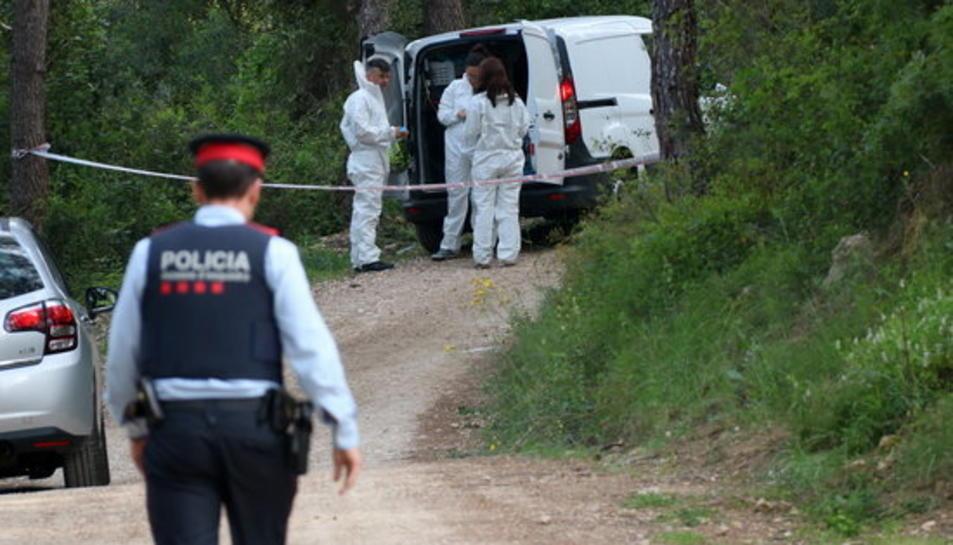 Pla general de la policia científica equipant-se per accedir al lloc on s'ha trobat un cos calcinat al costat del Pantà de Foix. En primer pla, un agent dels Mossos d'Esquadra. Imatge del 5 de maig de 2017
