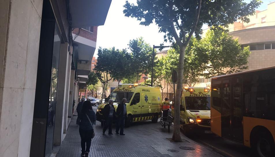 Imatge de les dues ambulàncies del SEM junt a l'autobús urbà atenent a les persones ferides en el lloc dels fets.