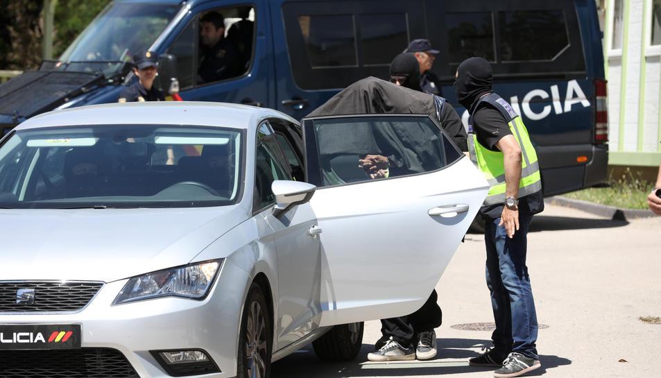 L'home es va cobrir la cara quan era traslladat al cotxe policial.