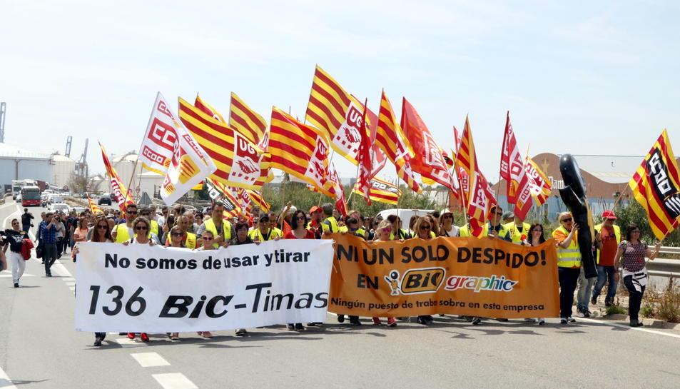 Pla general dels treballadors de BIC Graphic a Tarragona, fent una marxa lenta encapçalada per pancartes de protesta a l'autovia de Salou, amb el trànsit aturat al fons. Imatge del 9 de maig del 2017