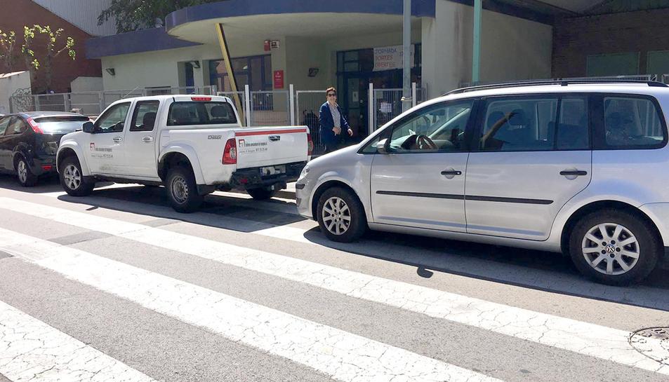 Vehicles estacionats sobre el pas de vianants al davant de l'escola del Serrallo.