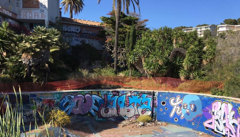 La piscina amb el xalet al fons.