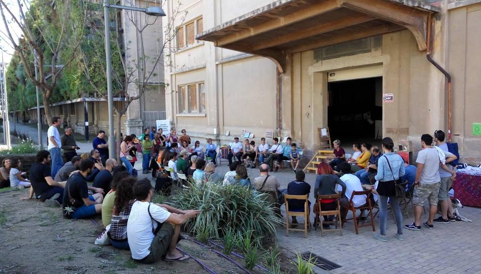 Una cinquantena de persones han participat en l'assemblea davant la porta oberta del magatzem 6.