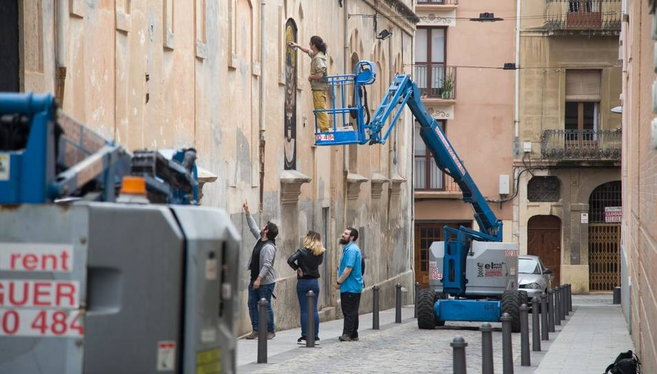 Un graffiter pintant una de les finestres tapiades del carrer de Pere Òdena.