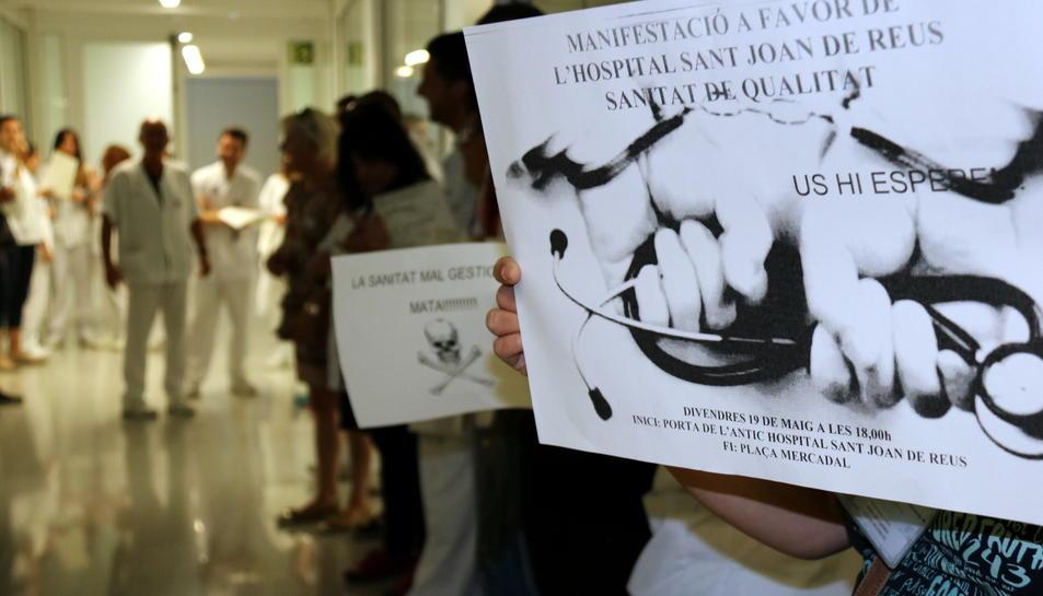 Pla detall d'una professional de l'Hospital Sant Joan de Reus, aguantant un cartell  en el qual es fa una crida a la manifestació per reivindicar els drets dels treballadors, i altres treballadors al fons, el 19 de maig del 2017
