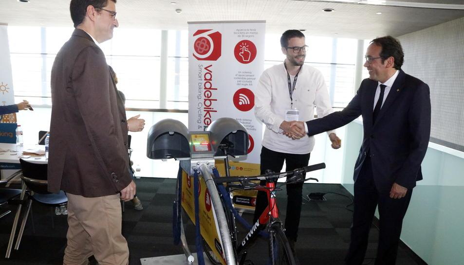 Pla obert del conseller de Territori i Sostenibilitat, Josep Rull, encaixant les mans amb els responsables d'una empresa que ofereix solucions d'aparcament per a bicicletes, a firaReus, el 19 de maig del 2017
