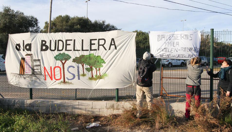Uns veïns van penjar una pancarta en contra del Pla Parcial Urbanístic de la Budellera, abans de fer una marxa reivindicativa.