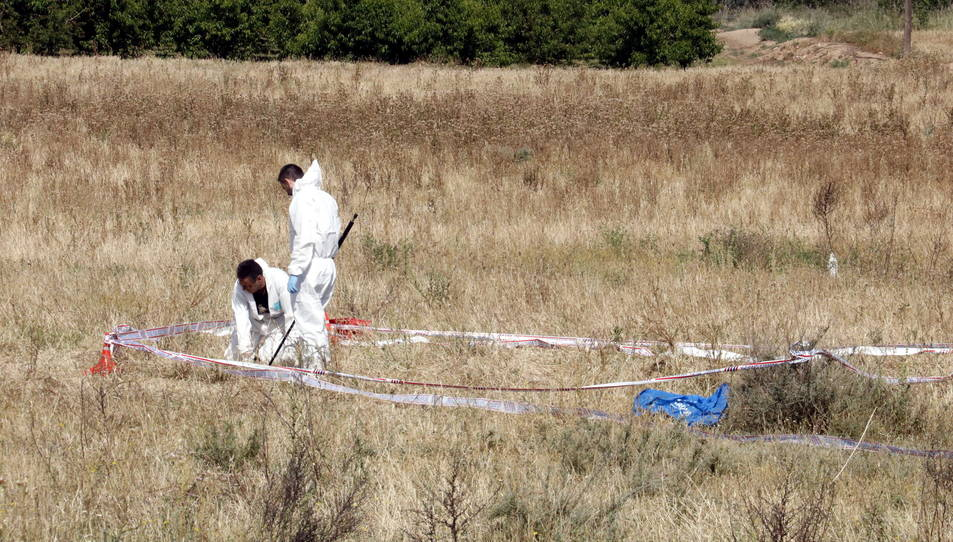 Primer pla de Mossos d'investigació analitzant el lloc dels fets, a la Bordeta.