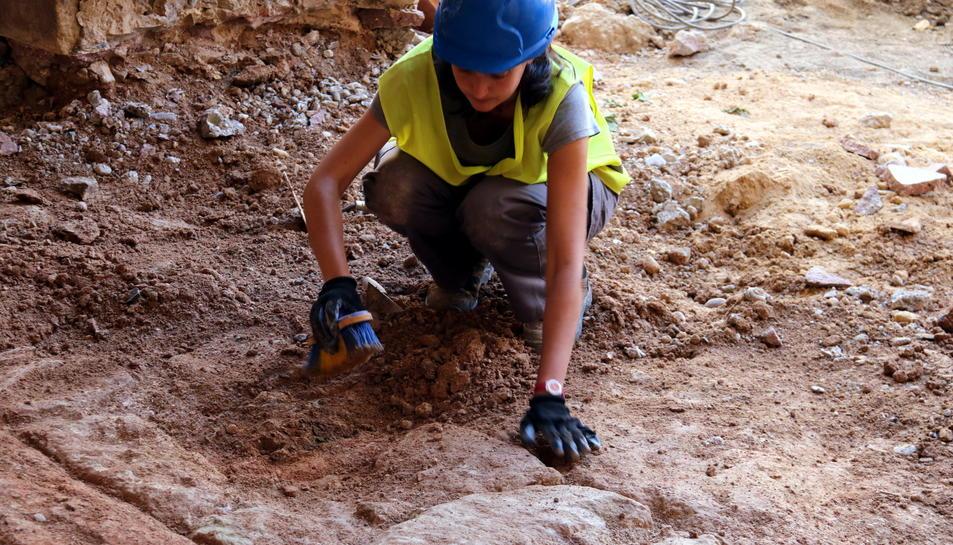 Una arqueòloga excava un mur aparegut davant de l'actual edifici de l'Ajuntament d'Horta de Sant Joan en les obres dels carrers del nucli antic. Imatge del 17 de maig de 2017 (horitzontal)